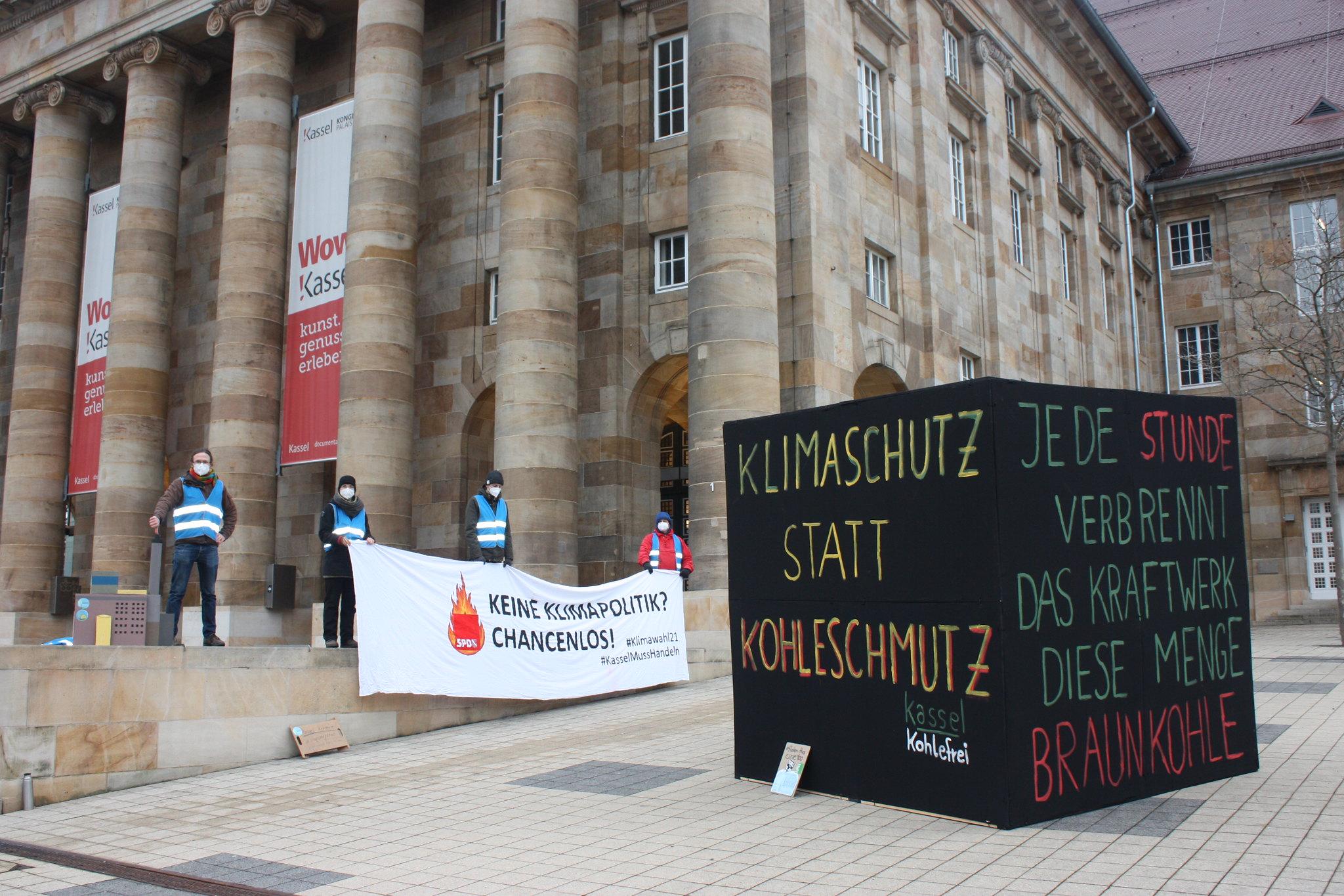 kohlefrei-Aktive vor der Stadthalle mit großem schwarzen Würfel: