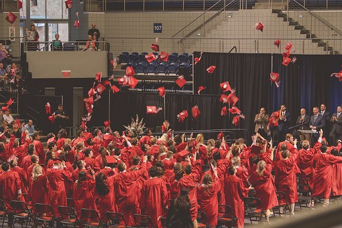 High school graduation ceremony, with students throwing their caps in the air. From Through the Eyes of an Educator: Changing of the Guard