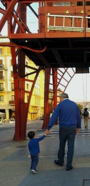 Caminando juntos y de la mano, nieto y aitxitxe bajo el Puente Colgante