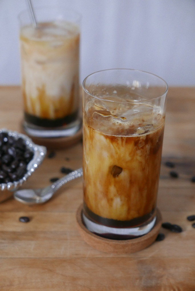 Two glasses of homemade iced latte next to a bowl of espresso beans.