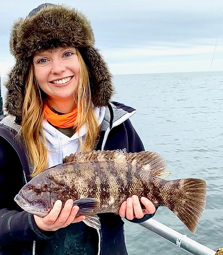 Photo of woman holding a perch she caught.