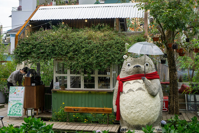 Human Size Japanese Character Totoro with Red Scarf and Transparent Umbrella in front of a Wooden House at Still Cafe in Da Lat, Vietnam