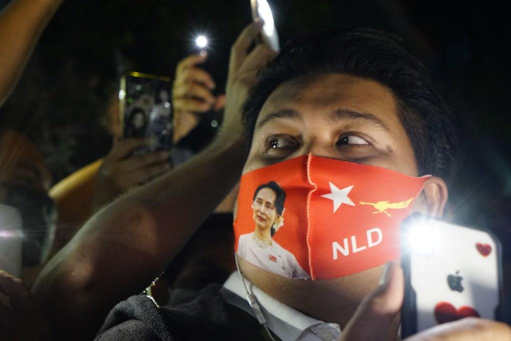 ประชาชนสวมหน้ากากที่มีภาพอองซานซูจีและชื่อพรรค NLD