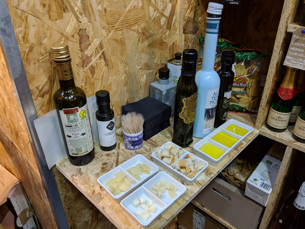 An olive oil tasting: three bottles of olive oil with three saucers in front, filled with oil. Next, there is a white saucer with pieces of crusty bread.