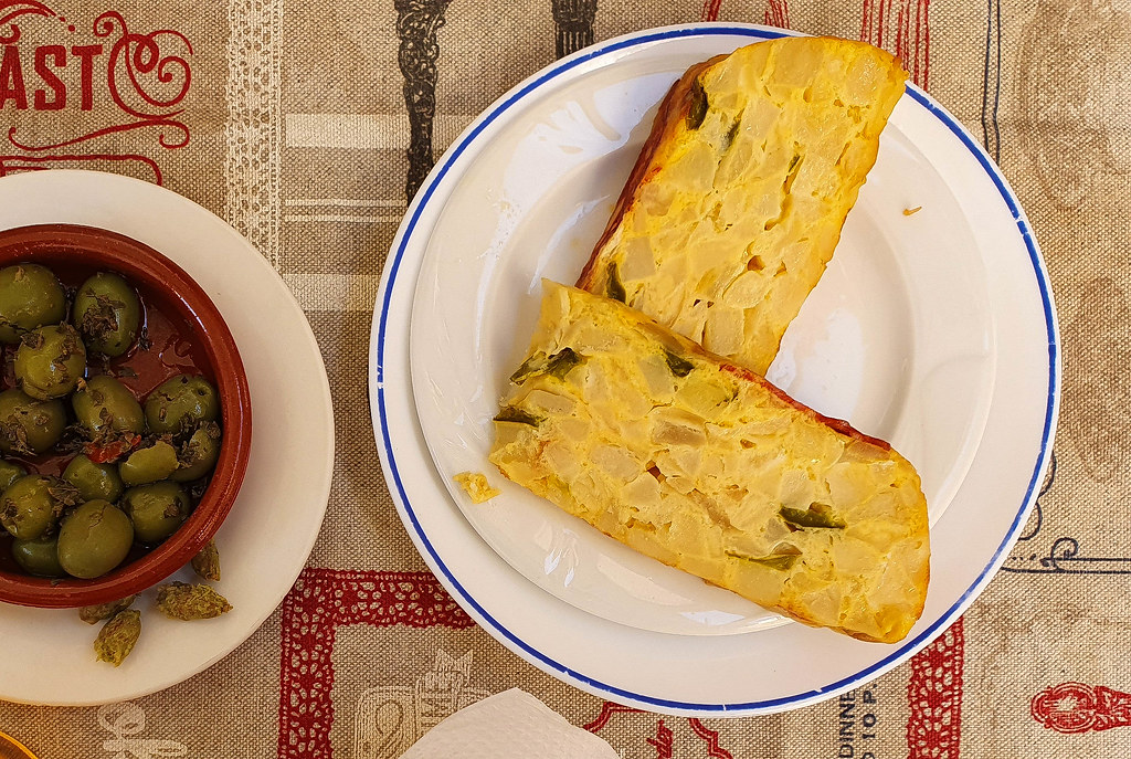 Two slices of potato and green pepper Spanish omelette, on a white plate with a blue border. Next to it, on the left, there is a bowl of green olives dressed with oregano.