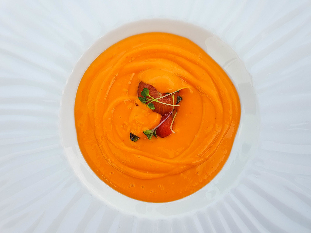 A close up of a bowl of orange salmorejo. In the middle of it there are tomato pieces and a few green microherbs