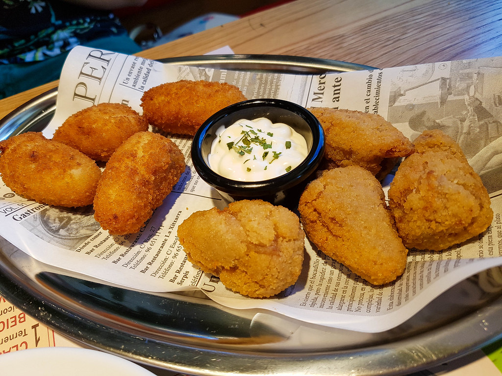 A long plate covered with a newspaper page, on top of which there are eight croquettes. In the middle there is a small black bowl filled with white aioli, with chopped green parsley on top.