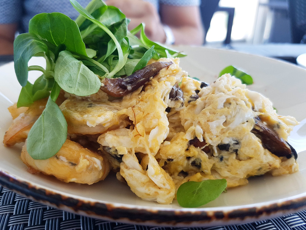 A plate of scrambled eggs with mushrooms. On top there is a bunch of fresh green spinach laves.