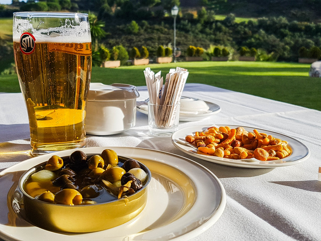 A brown terracotta bowl with green olives, next to one filled with peanuts, set on a white table. Next to them there is a pint of yellow San Miguel beer.