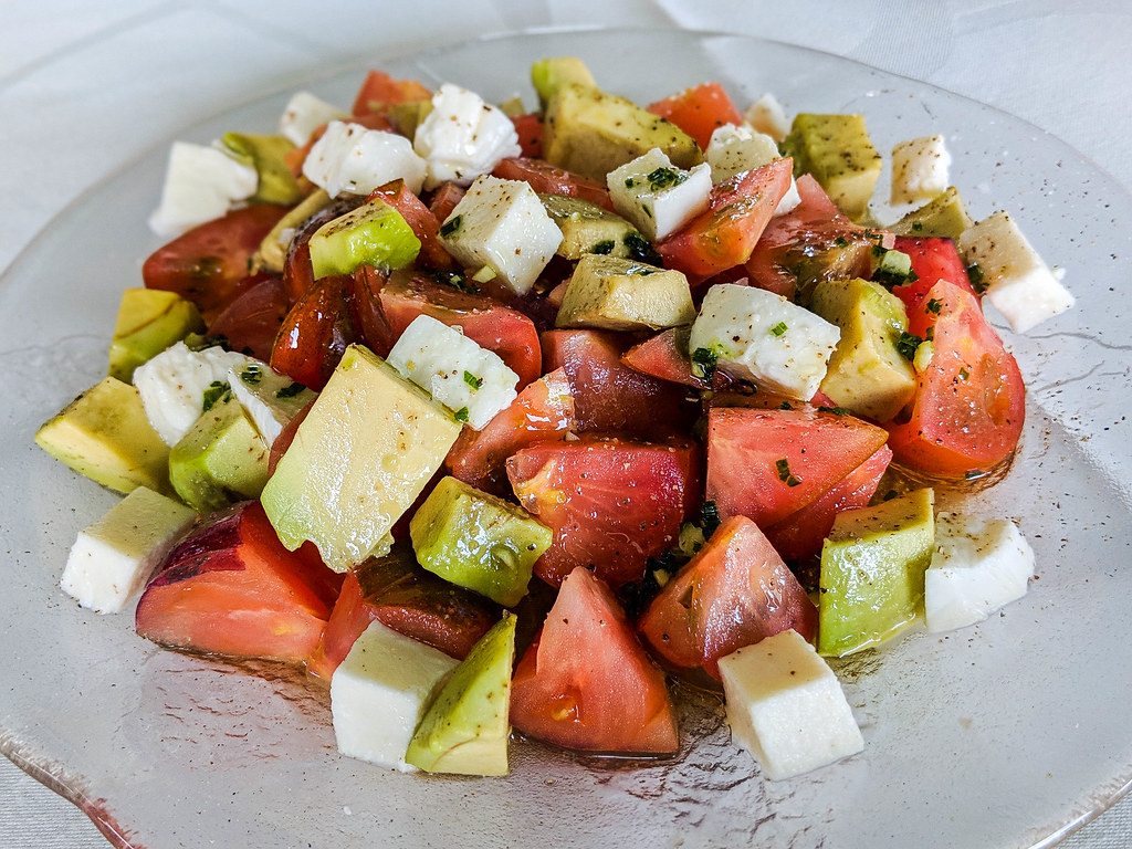 A plate of avocado, tomatoes and white cheese salad, topped wit ha green herbs dressing