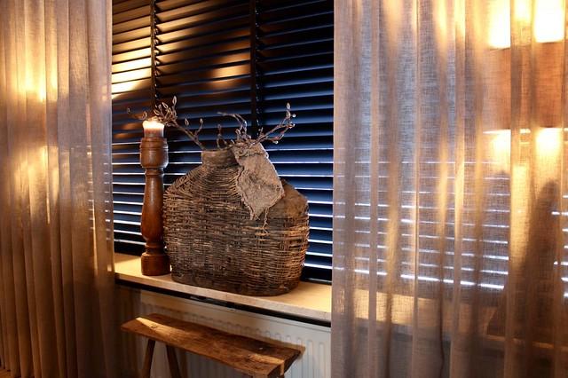 Grote leemkruik met houten kandelaar op vensterbank