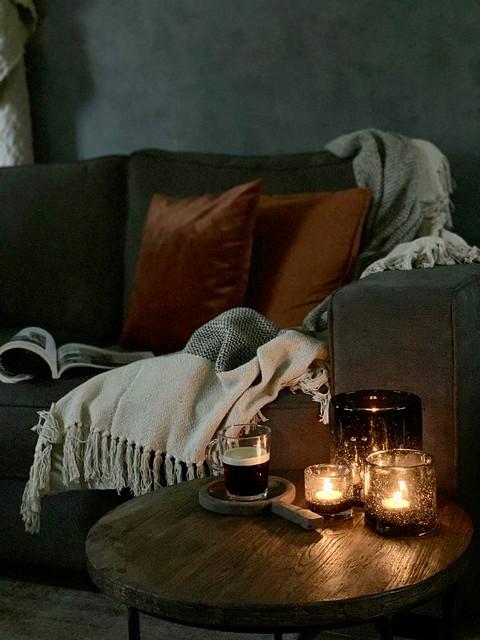 Oranje bruine kussens bijzettafel glazen windlicht koffie op plankje