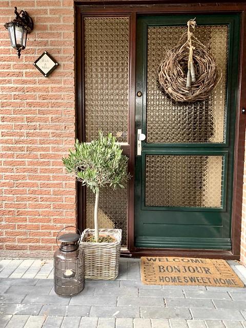 Groene voordeur olijfboompje in rieten mand windlicht krans