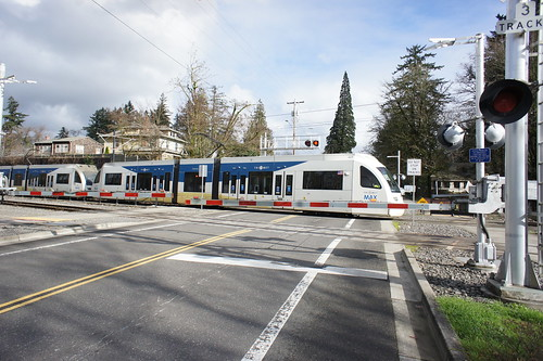 A southbound train zips across Harrison St in Milwaukie