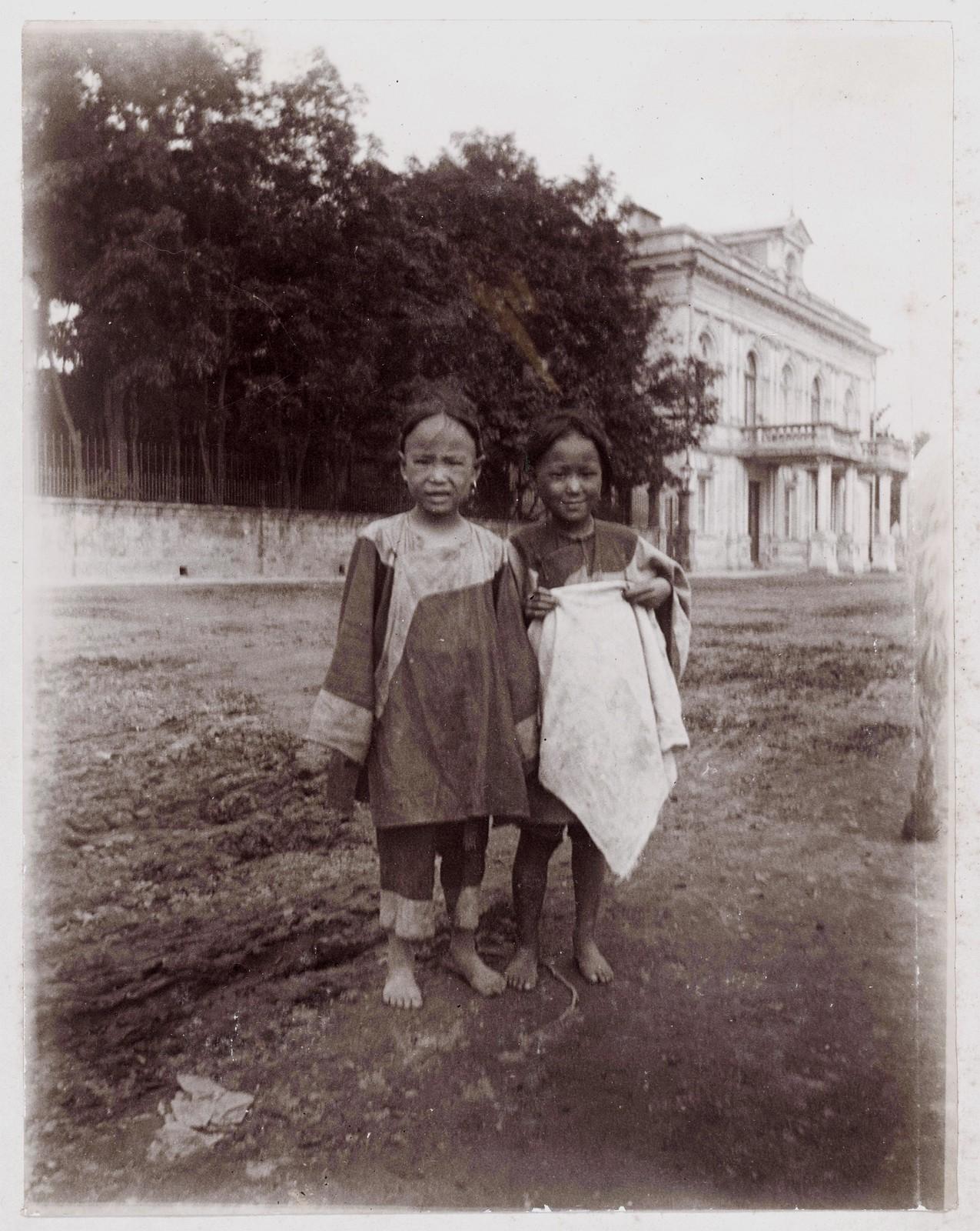Двое босоногих детей стоят на грязной улице перед большим домом Линдхольмов, улица Шефнеровская