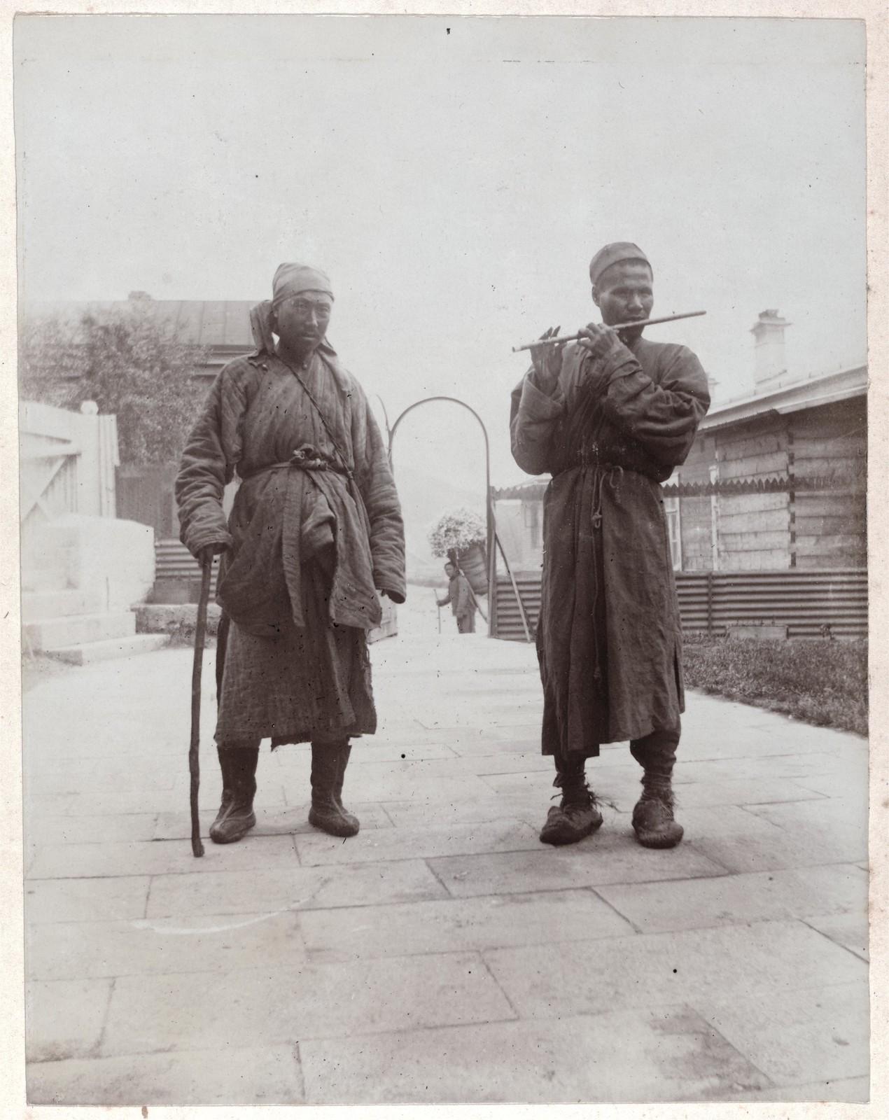 Два уличных артиста китайских музыкантав во дворе Дома Смита