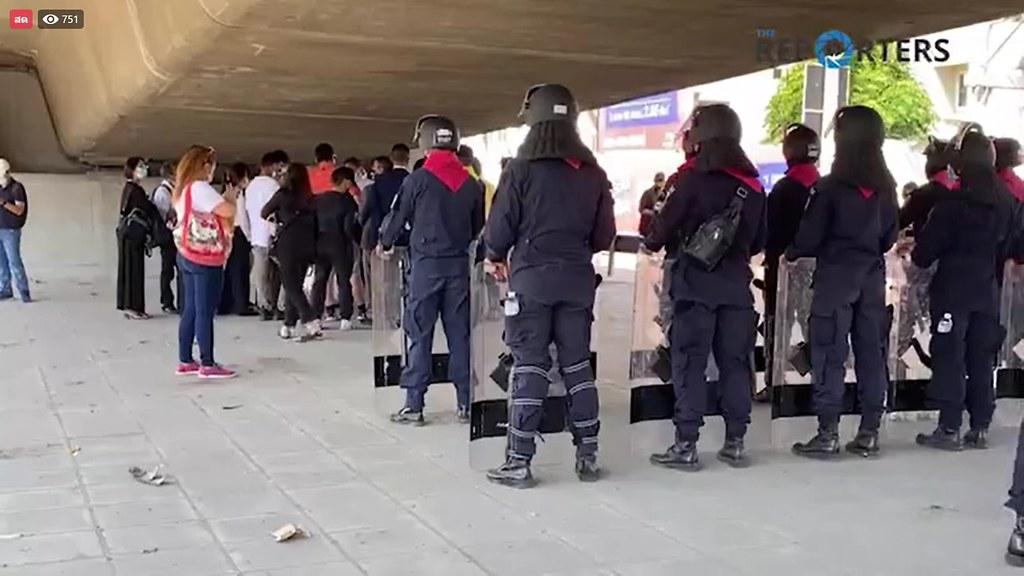 ตำรวจชุดคุมฝูงชนยืนคุมขณะที่ทนายความและผู้ที่ถูกดำเนินคดีกำลังปรึกษาแนวทางคดี