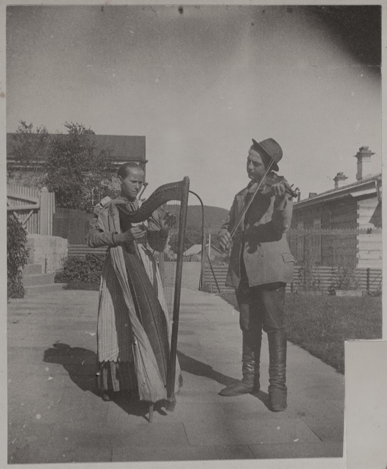 Уличные музыканты с арфой и скрипкой