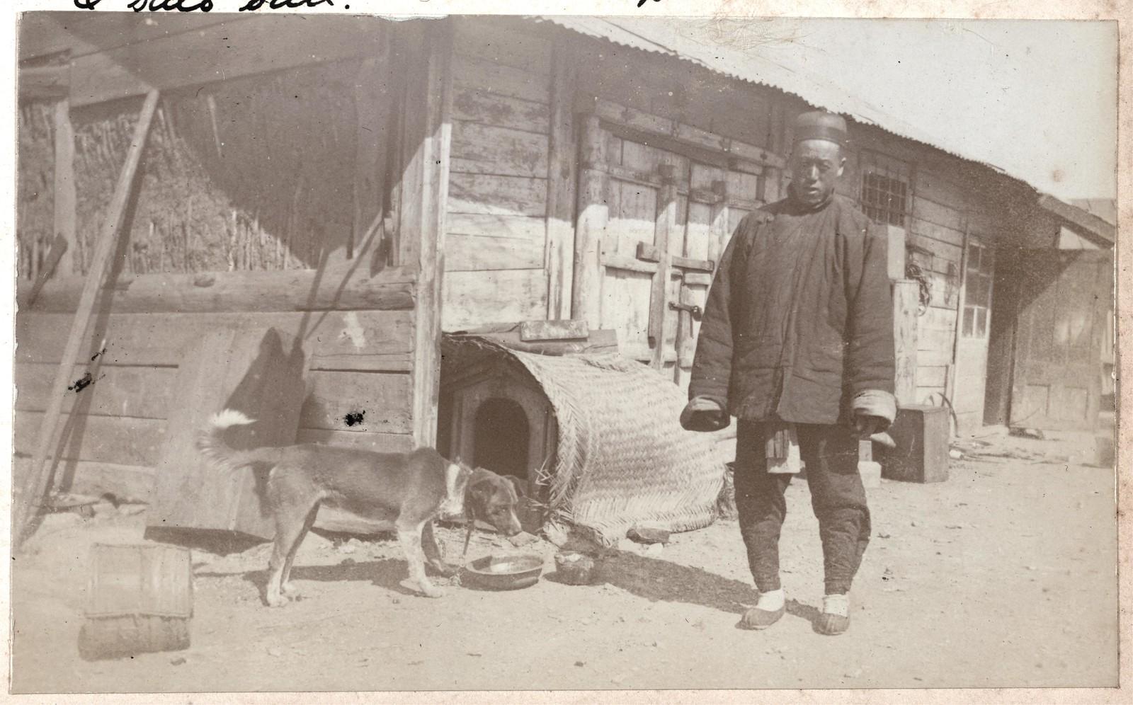 Доу Ки с собакой Бочкой, стоящие возле сараев и собачьей будки в верхнем дворе дома Смитов