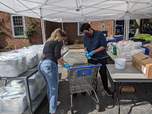The Williamsburg Engagement team from W&M worked at outdoor tables under a tent at the House of Mercy to assemble items for each guest, such as food, hygiene products & pet food, and put them into a cart.