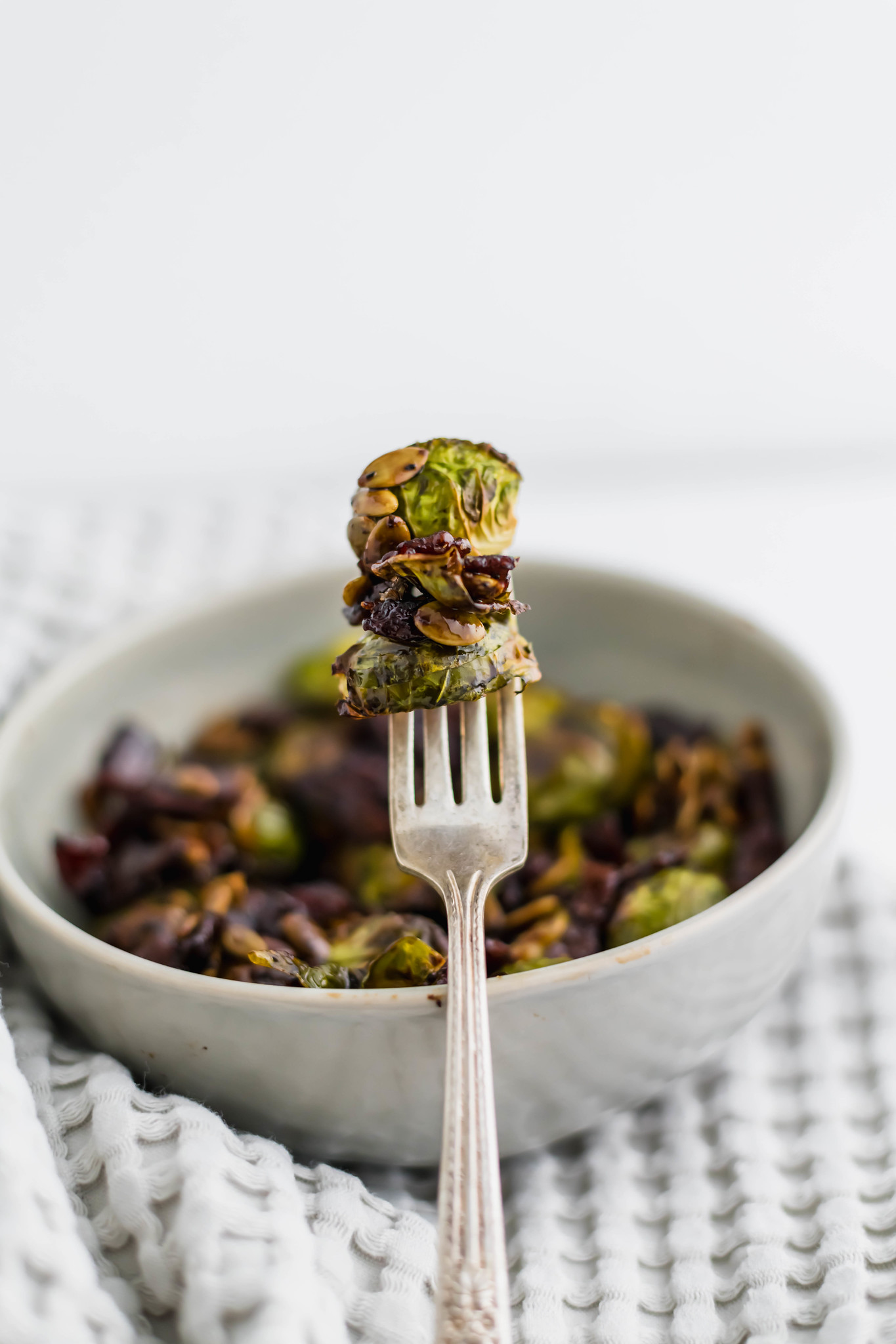 Honey Balsamic Brussels Sprouts are roasted perfectly in the oven then drizzled with the tastiest sweet and savory sauce. Topped with crispy bacon and pumpkin seeds for the perfect crunch.
