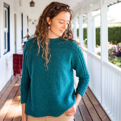 Skiddaw is an oversized sweater featuring a striking cable design along the sleeves and neck.