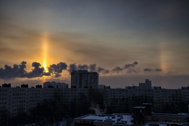Light pillar and a rainbow over the dawn city