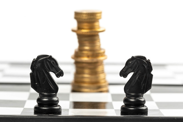 Two chess horses on a chessboard and a king of coins in the background, business and money concept