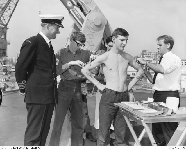 On board HMAS Perth (II) D38, at Garden Island, NSW, crew members are receiving inoculations