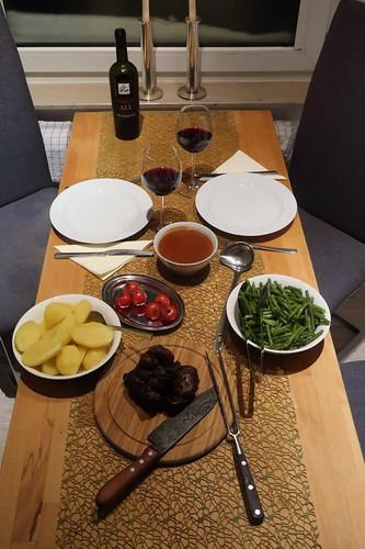 Lammkeule mit Butterbohnen, geschmorten Tomaten und Salzkartoffeln (Tischbild)