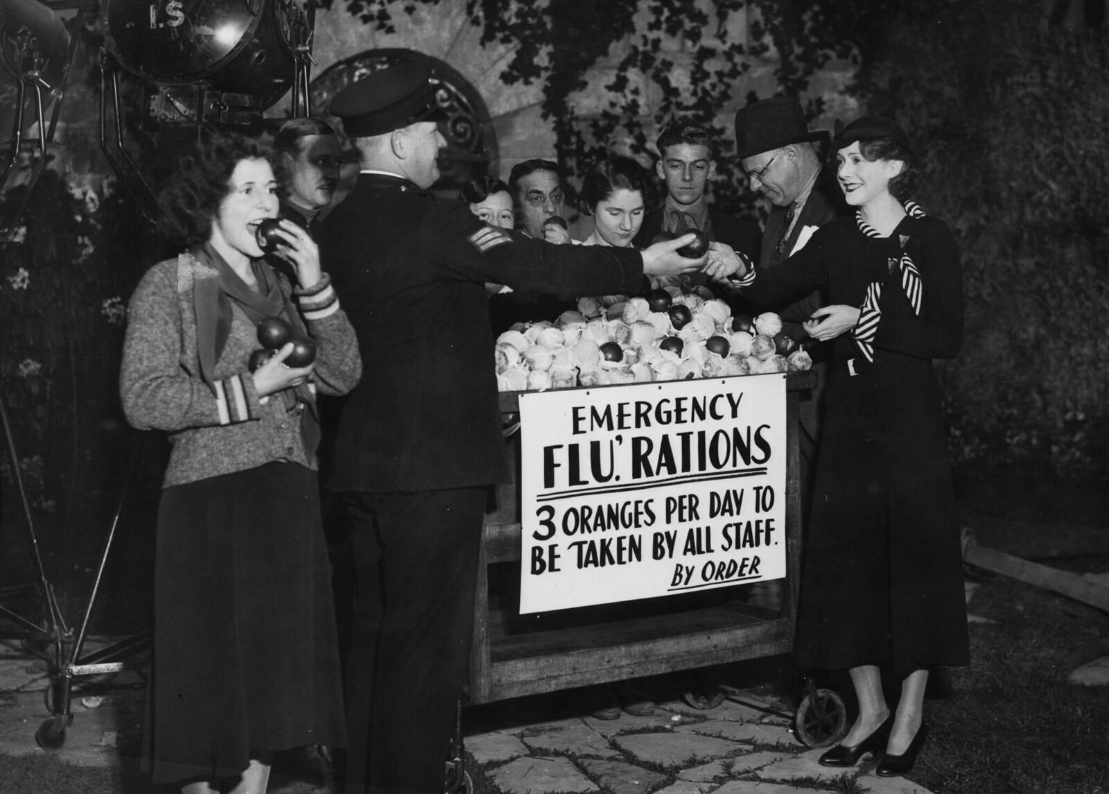 1940.  Актриса Молли Ламонт получает свой апельсиновый «паек» от сержанта в студии «Элстри» в Лондоне. Сообщается, что все съедают три апельсина в день после эпидемии гриппа, унесшей более 200 жертв на студиях
