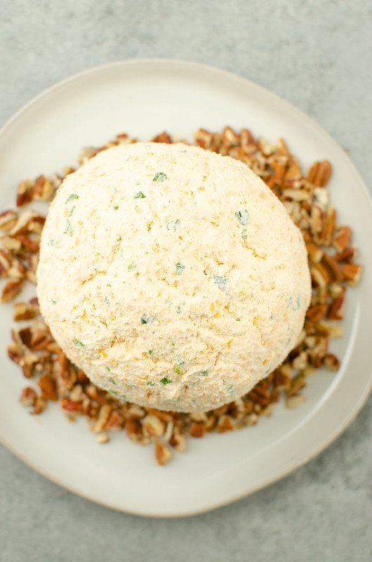 Cheese ball on top of pecans on a white plate