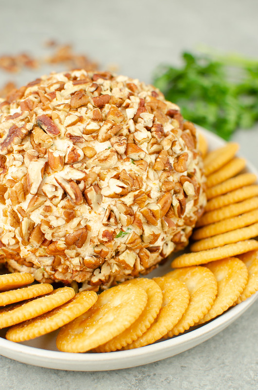 Cheese ball rolled in pecans surrounded by crackers on a white plate