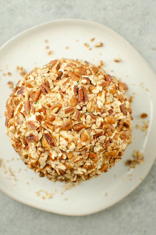 Cheese ball covered in pecans on a white plate with extra pecans on plate