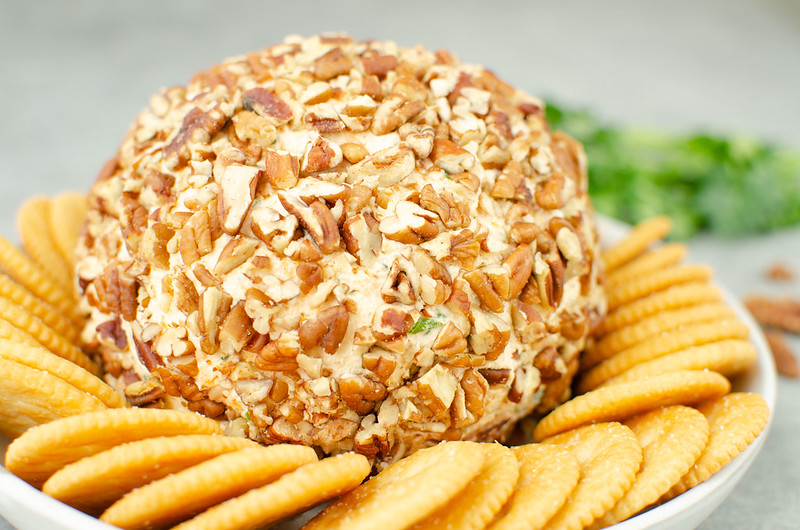 Cheese ball coated in pecans with Ritz crackers around it and parsley in the background