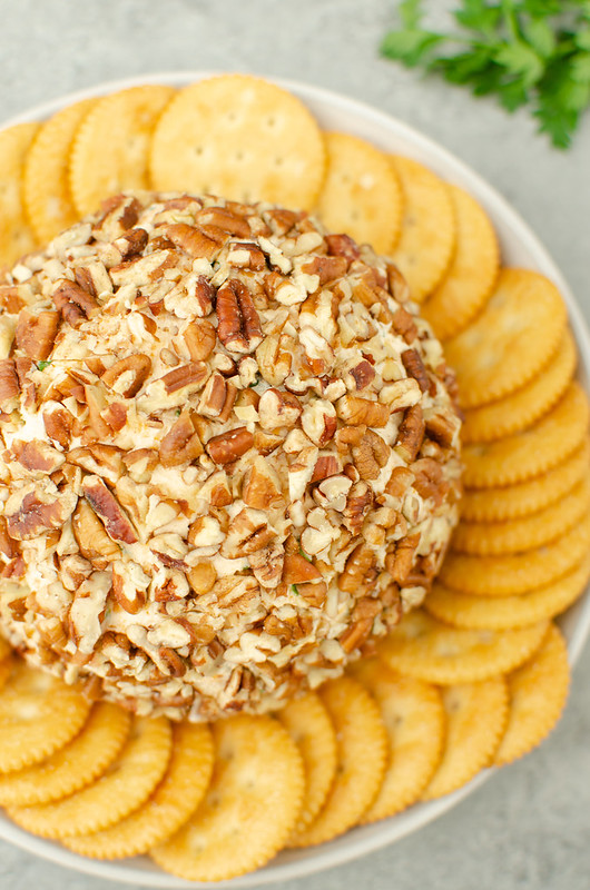Overhead shot of pecan cheese ball on a white plate with buttery crackers around it