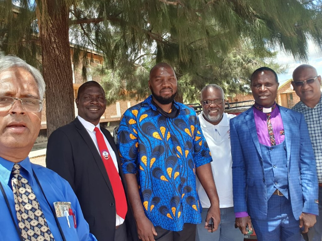 Six men stand smiling for photo after church.