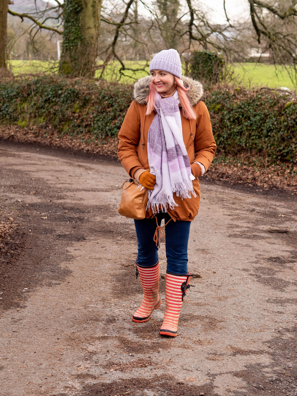 The Importance of Bright Accessories in Cold Weather | Catherine Summers of Not Dressed As Lamb, Over 40 Fashion, wearing burnt orange parka, lilac beanie and scarf and blue jeans tucked into red striped wellies