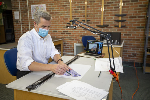 Matthew Allar, associate professor of theatre at W&M, draws at a drafting table with camera overhead that projects the view onto screens for students in his Fundamentals of Theatrical Design course to follow along with remotely.