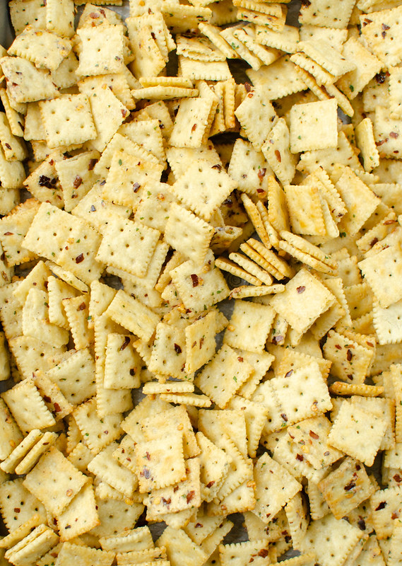 Mini Saltine crackers in buttery spicy ranch seasoning on a baking sheet