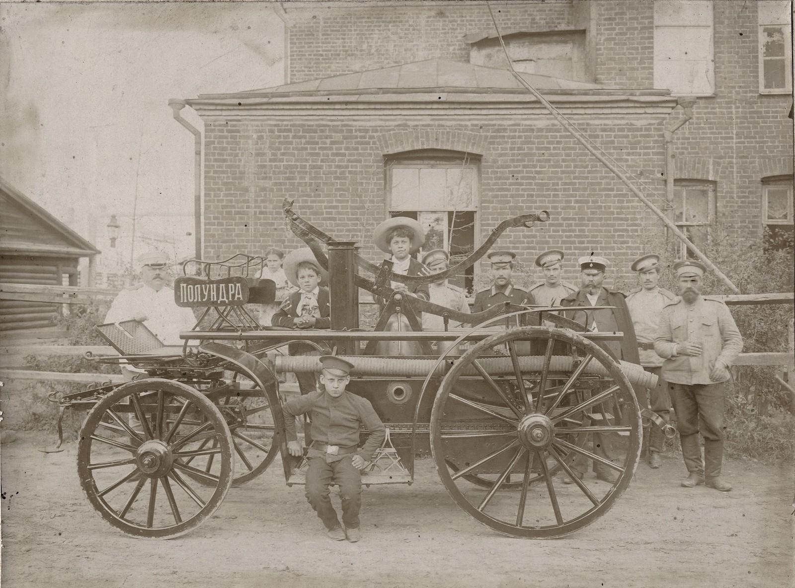 1910. Группа пожарных служителей с ручным двухцилиндровым насосом, установленным на колесном шасси пролетки