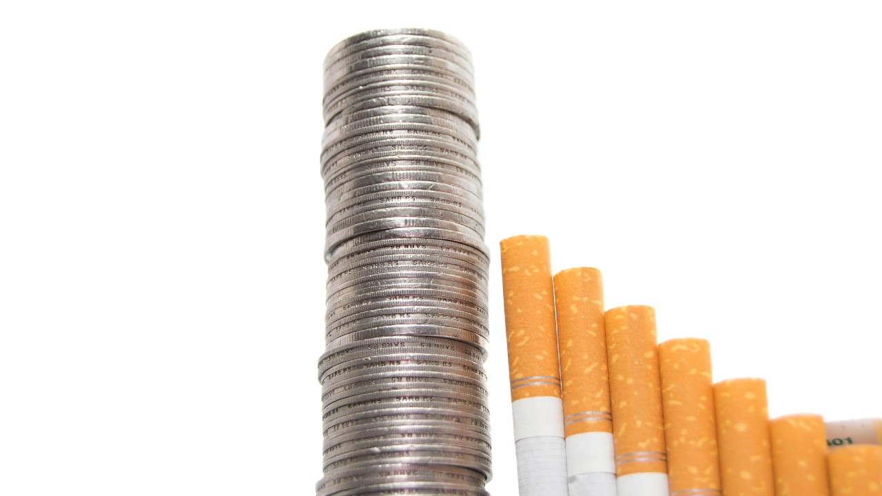 Image of cigarettes and tower of coins