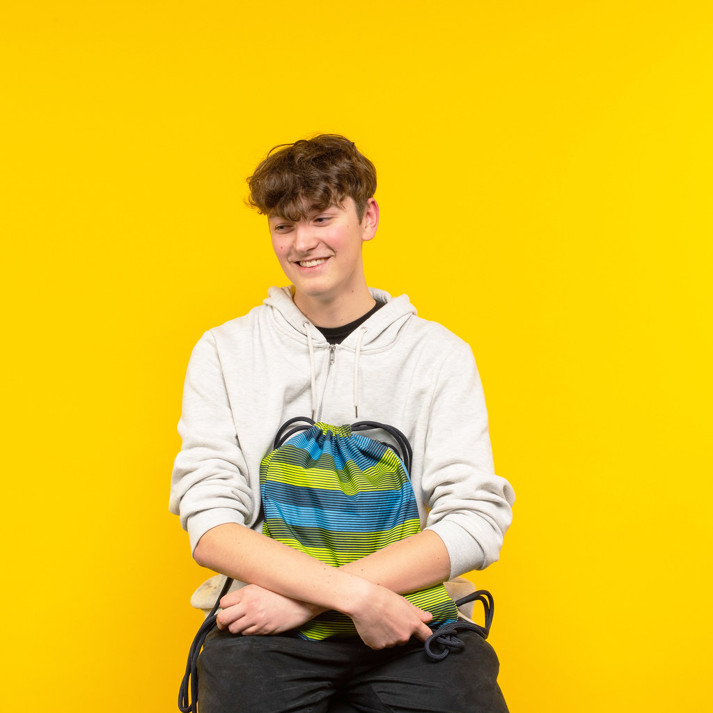 Ed sitting on a chair in front of a yellow background