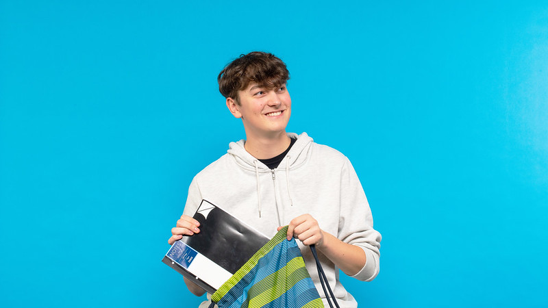 A young man smiling while putting a book in a rucksack.