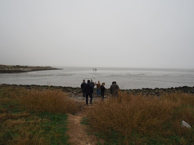 A group of researchers stands close to a waterway.