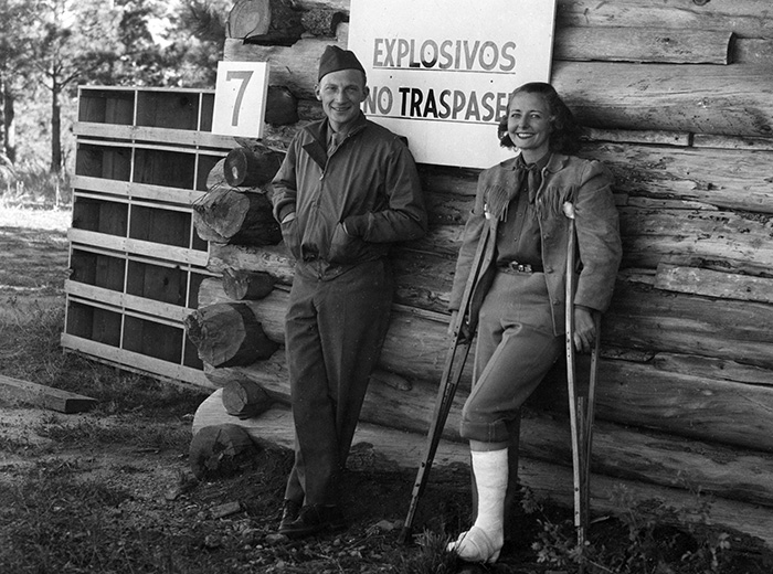 a man and woman in front of a log cabin