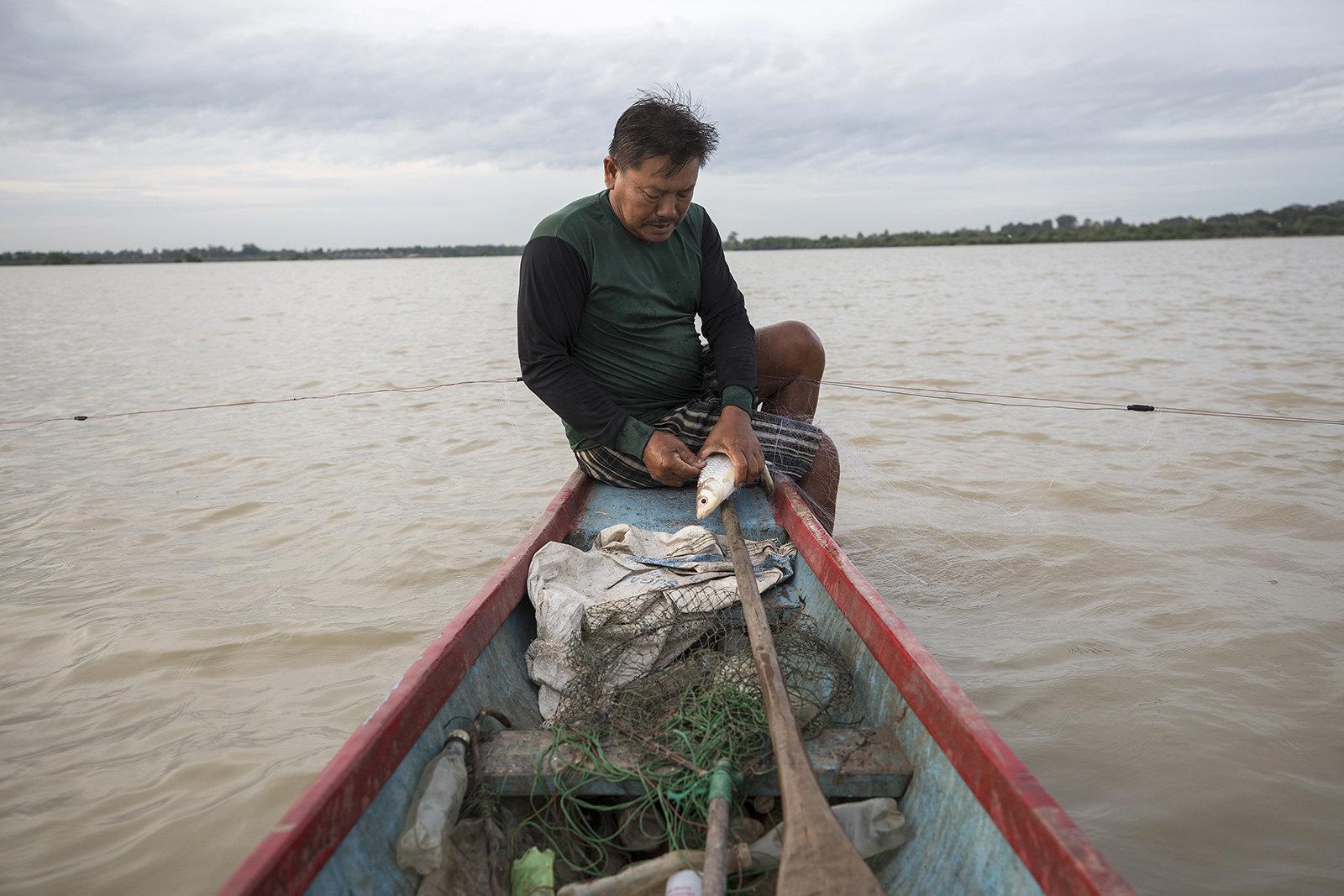 สุนันท์ ผาชุม อายุ 53 ปี ระหว่างจับปลาท้ายเขื่อน ชุมชนที่เขาเคยอาศัยได้รับผลกระทบจากการสร้างเขื่อนราษีไศล หลังที่ดินถูกน้ำท่วม เขาต้องลงทุนกว่า 6 หมื่นบาทเพื่อซื้อปลาและอุปกรณ์จับปลาที่ใช้ได้กับระดับน้ำลึก เขาไม่แน่ใจว่าจะใช้เวลานานแค่ไหนจึงจะคืนทุนได้(ที่มา: Luke Duggleby)