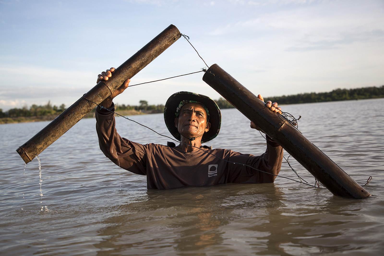 ทองอินทร์ นงรักษ์ ใช้อุปกรณ์ดักจับปลา ทั้งนี้อุปกรณ์ดักจับปลาท้องถิ่นใช้การไม่ได้อีกต่อไป เมื่อแม่น้ำกลายสภาพเป็นเขื่อน (ที่มา: Luke Duggleby)