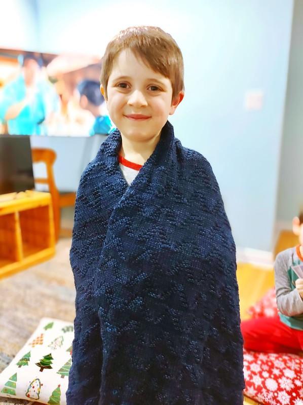 Felix loves the bigger Seaside Baby Blanket by Leelee Knits that Nikki knit him using Malabrigo Rios!