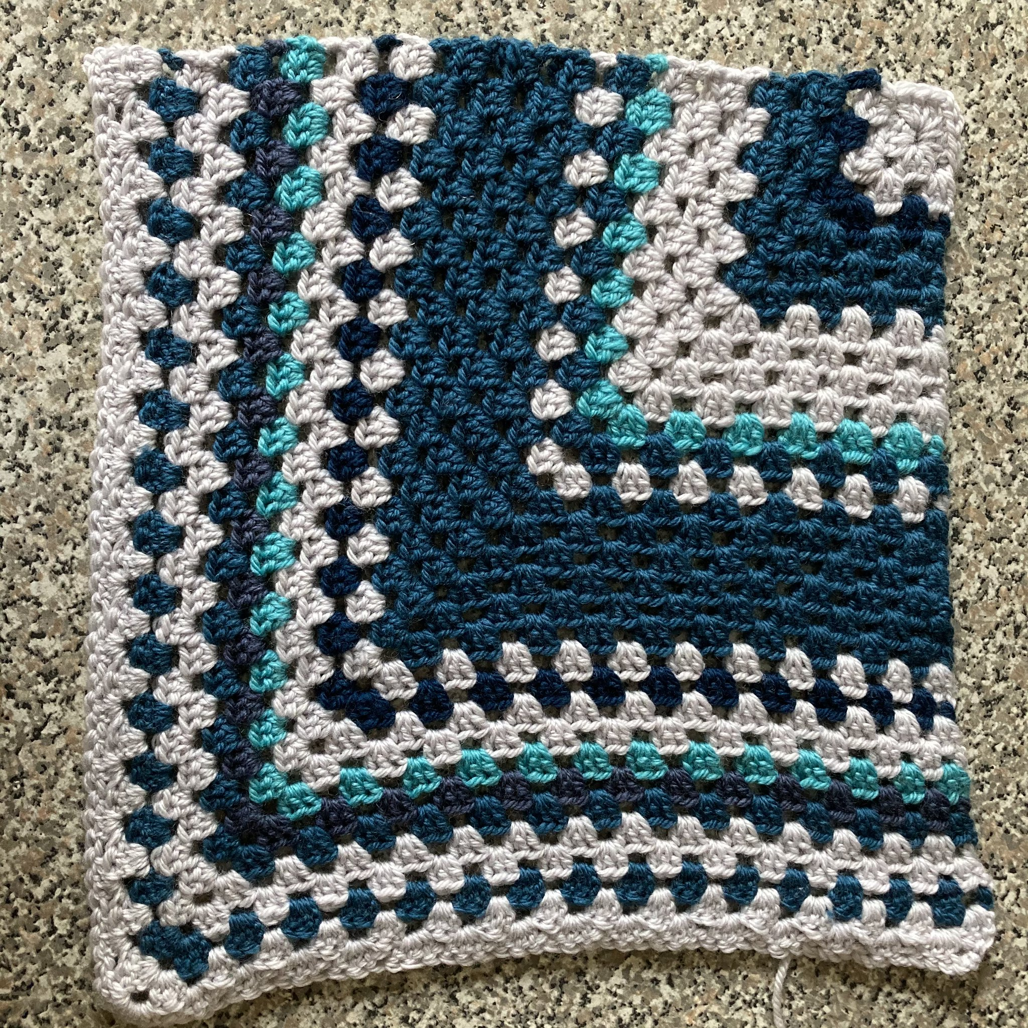 crocheted temperature blanket square with blue and grey yarns